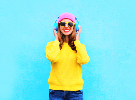 Fashion pretty cool smiling girl listening to music in headphones wearing colorful pink hat, yellow sunglasses and sweater over blue background Stok Fotoğraf