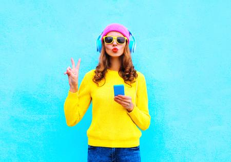 파란색 배경 위에 화려한 분홍색 모자 노란색 스웨터 선글라스를 착용하고 스마트 폰으로 헤드폰에서 패션 꽤 달콤한 평온한 여자 듣는 음악 스톡 콘텐츠