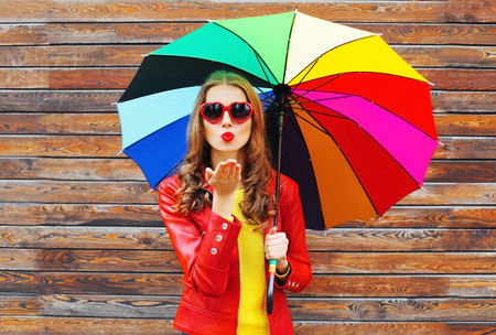Fashion pretty woman with colorful umbrella sends air sweet kiss in autumn day over wooden background wearing a red leather jacket Standard-Bild