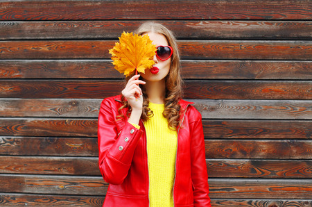Portrait pretty young woman with autumn yellow maple leafs wearing a red leather jacket over wooden background