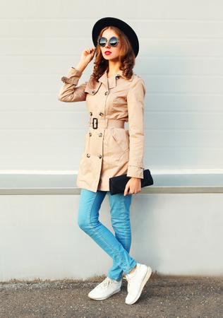 Arbeiten Sie die hübsche Frauenmodellaufstellung um, die einen Mantel und eine Handtasche des schwarzen Hutes über grauem Hintergrund trägt Standard-Bild - 64403045