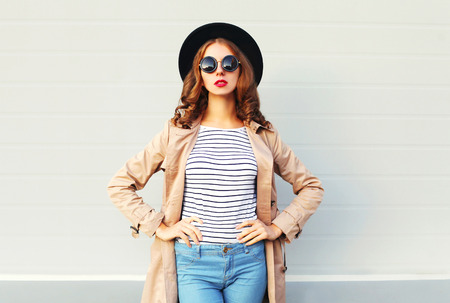 Fashion pretty woman with red lips wearing a black hat sunglasses over grey background