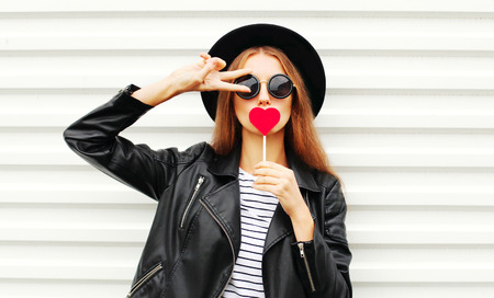 Cool young girl with red lollipop heart wearing fashion black hat leather jacket over white urban background Stok Fotoğraf - 64403074