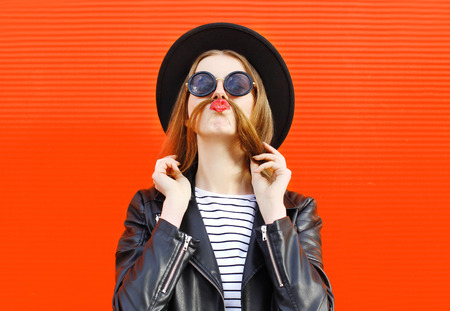 Fashion funny woman having fun shows moustache hair over colorful red background
