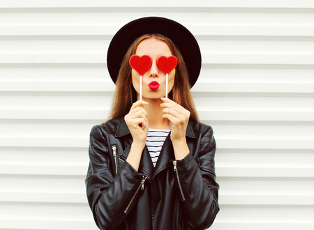 Fashion portrait pretty sweet young woman with red lips making air kiss with lollipop heart wearing black hat leather jacket over white background 版權商用圖片 - 64403173
