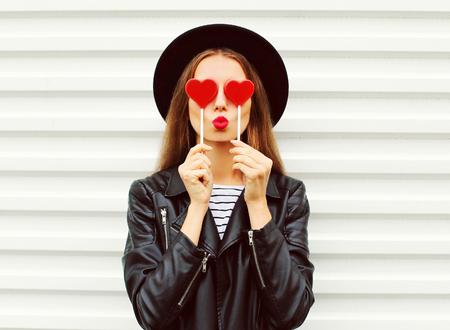 Moda ritratto dolce giovane donna con le labbra rosse facendo bacio dell'aria con il cuore lecca-lecca vestita di nero, giacca di pelle cappello su sfondo bianco