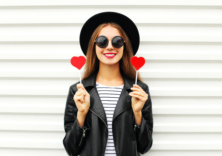 Fashion pretty sweet young smiling woman with red lips holds lollipop heart wearing black hat leather jacket over white background Stok Fotoğraf