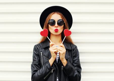 Fashion pretty sweet young woman with red lips making air kiss with lollipop heart wearing black hat leather jacket over white background Standard-Bild