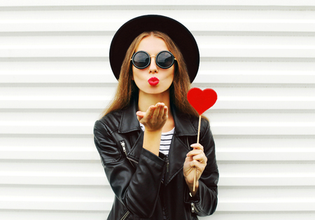 Fashion pretty sweet young woman with red lips sends air kiss with lollipop heart wearing black hat leather jacket over white background Stok Fotoğraf - 64403188