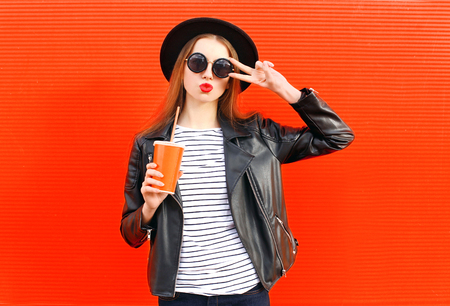 Fashion pretty young woman with fresh fruit juice cup in black rock style having fun over colorful red background