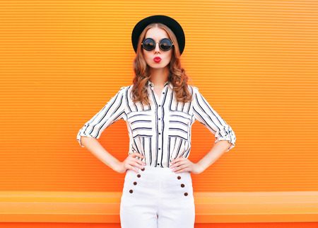 Fashion pretty glamour woman wearing a black hat sunglasses white pants over colorful orange background