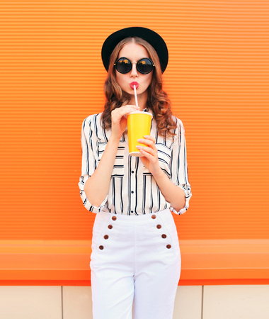 Fashion pretty woman model with fresh fruit juice cup wearing black hat white pants over colorful orange background