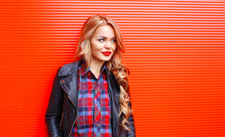 over black: Fashion portrait pretty blonde woman wearing black rock style over colorful red background