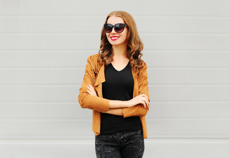 Fashion portrait happy smiling woman with crossed arms wearing a sunglasses, jacket over grey background
