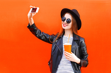 over black: Fashion pretty smiling young woman taking picture self portrait on smartphone in black rock style over city red background Stock Photo