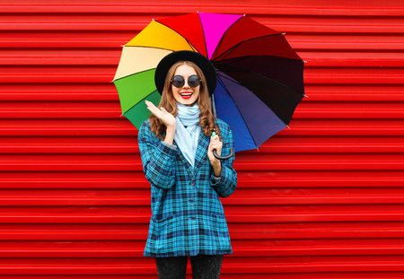 Fashion cheerful smiling woman holds colorful umbrella wearing black hat checkered coat jacket over red background