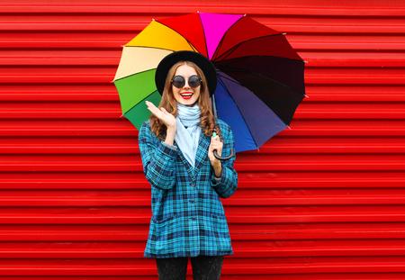 Mode fröhlich lächelnde Frau hält bunten Regenschirm schwarzen Hut trägt karierten Mantel Jacke auf rotem Hintergrund Standard-Bild