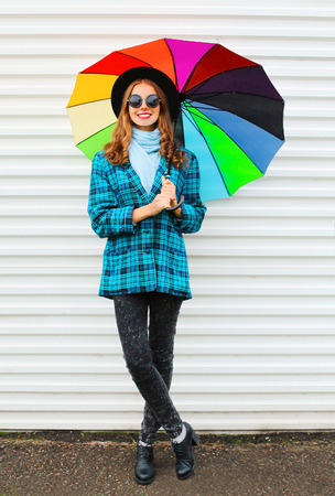 Fashion happy pretty smiling woman with colorful umbrella wearing black hat checkered coat jacket over white background