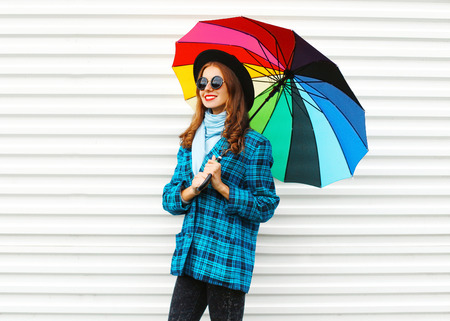 Fashion pretty smiling woman holds colorful umbrella wearing black hat checkered coat jacket over white background Stok Fotoğraf