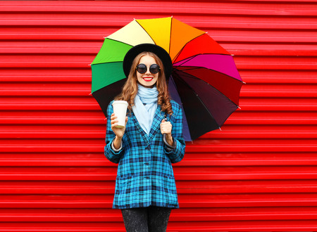 Fashion pretty young smiling woman with colorful umbrella coffee cup wearing a black hat coat jacket over red background Stok Fotoğraf