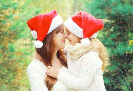 newyear: Christmas family child hugging mother in santa red hats together over a tree