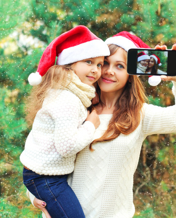 Christmas smiling mother and child taking picture self portrait on smartphone together over snowflakes
