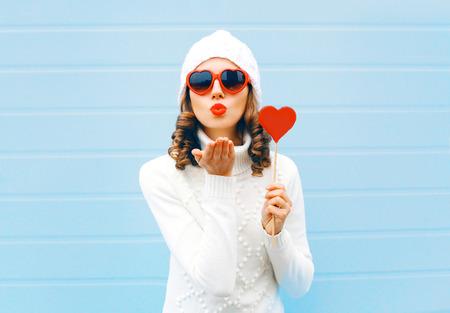 빨간 입술을 불고 세로 예쁜 여자 공기 키스 파란색 배경 위에 롤리팝 심장 모양의 선글라스를 착용하는 마음, 니트 모자, 스웨터를 보유하고 전송