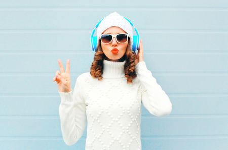 Happy woman listens to music in headphones wearing a sunglasses, knitted hat, sweater over blue background, blowing lips having fun Stok Fotoğraf