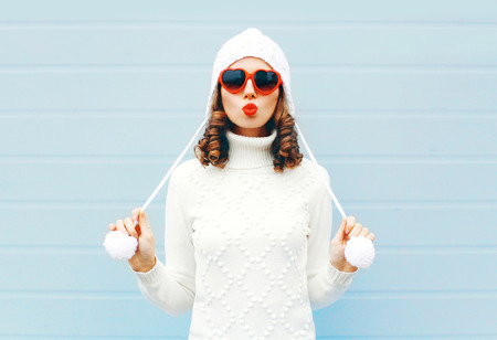 Happy young woman blowing red lips makes air kiss wearing a heart shape sunglasses, knitted hat, sweater over blue background Standard-Bild