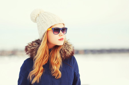 Fashion winter portrait pretty blonde woman wearing a jacket hat and sunglasses looks away over snowy background