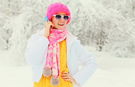 newyear: Fashion winter woman talking on smartphone wearing colorful knitted hat scarf over snowy trees