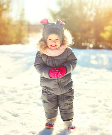 Winter portrait funny smiling child playing in sunny day