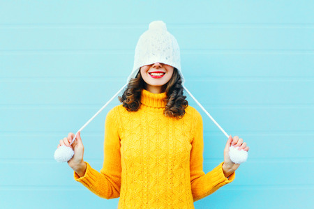 Fashion happy young woman in knitted hat and sweater having fun over colorful blue background Stok Fotoğraf - 68211811