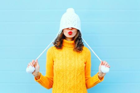 Feliz chica fresca soplando labios rojos hace beso de aire con un gorro de punto, suéter amarillo sobre fondo azul
