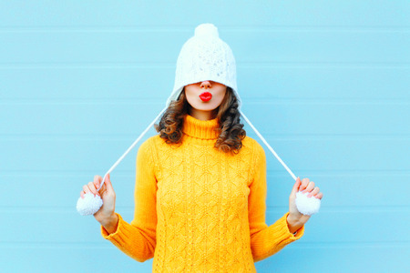 Happy cool girl blowing red lips makes air kiss wearing a knitted hat, yellow sweater over blue background 免版税图像 - 68211814