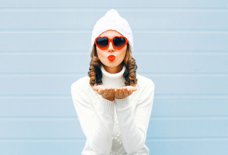 Happy woman blowing red lips sends air kiss wearing a heart shape sunglasses, knitted hat, sweater over blue background
