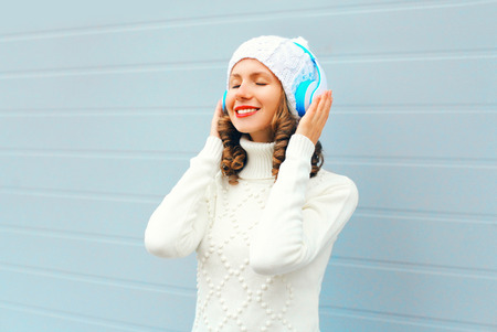 Happy young woman in headphones enjoys listens to music wearing a knitted hat, sweater over blue background Stock Photo - 68211887