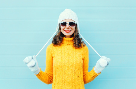 Portrait happy young smiling woman wearing a sunglasses, knitted hat, sweater over blue background Stock Photo - 68211888