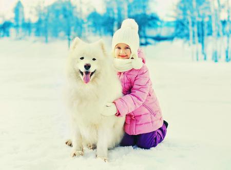 Happy smiling child with white Samoyed dog on snow winter