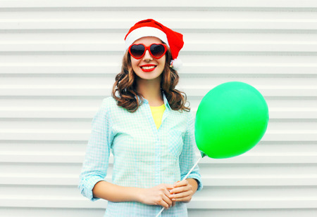 Portrait happy smiling woman in christmas red santa hat with air balloon over a white background Stock Photo - 68211930