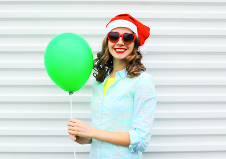 Portrait happy smiling woman in christmas red santa hat, with air balloon over white background Stock Photo - 68211931