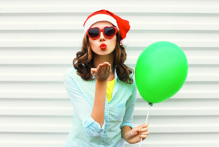 Portrait pretty woman in christmas red santa hat, with air balloon, heart sunglasses sends air kiss over white background Stock Photo - 68211932