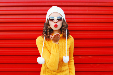 Fashion woman blowing red lips makes sends air kiss wearing colorful knitted sweater over red background