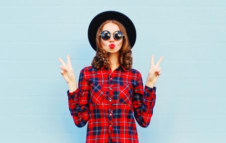 赤黒帽子をかぶってキス空気を作る赤い唇を吹いてファッションかなり若い女性は青い背景にシャツを格子縞