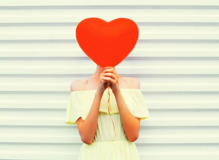 hides: Woman hides head red air balloon heart shape over white background