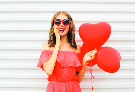 Cheerful young woman wearing red sunglasses with air balloons heart shape over white background