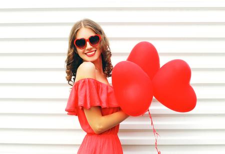 Felice giovane donna che indossa il vestito rosso e occhiali da sole a forma di palloni ad aria di cuore su sfondo bianco sorridente