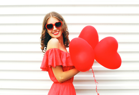 Happy smiling young woman wearing red dress and sunglasses with air balloons heart shape over white background