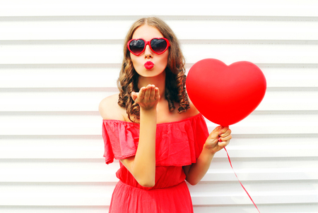 Portrait pretty woman in red dress sends air kiss with balloon heart shape over white background