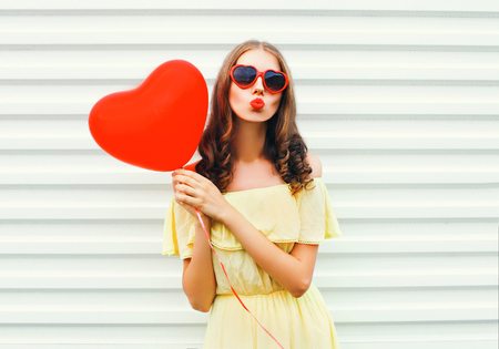 Portrait pretty woman with red lips sends kiss with air balloon heart shape over white background Stock Photo